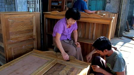 mestre : YANGON, MYANMAR - FEBRUARY 17, 2018: Production of handmade wooden furniture in family carpenter workshop in Chinatown, masters repair cracks in wood with wax filler stick, on February 17 in Yangon