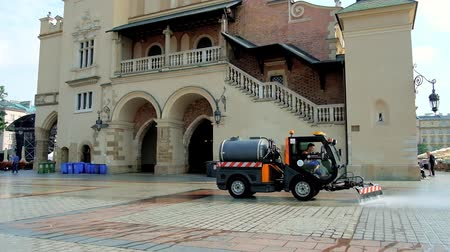 kamienice : KRAKOW, POLAND - JUNE 11, 2018: The busy morning in Main Market Square - the street sweeper vehicle washes area at the entrance to the Cloth Hall, on June 11 in Krakow. Stock Footage