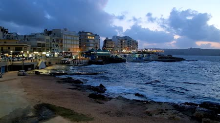 maltština : The evening coast of resort with stormy waves, bright illumination of seaside Islet Promenade, line of tourist hotels, cafes and souvenir stores, Bugibba, Malta. Dostupné videozáznamy