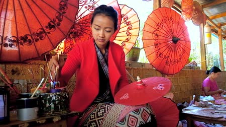 mianmar : PINDAYA, MYANMAR - FEBRUARY 19, 2018:  The Shan paper workshops master shows the art of creating traditional Burmese umbrellas, covered with beautiful floral patterns, on February 19 in Pindaya