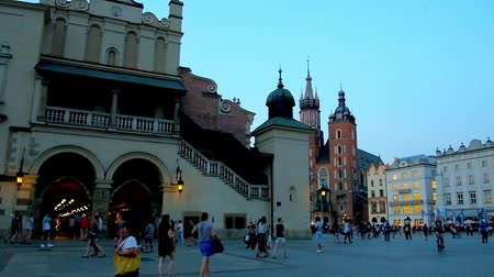 kamienice : KRAKOW, POLAND - JUNE 11, 2018: The evening walk along the Main Market Square with a view on the Cloth Hall (handicraft market), St Mary Basilica and historical townhouses, on June 11 in Krakow.