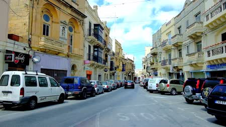 エディフィス : MOSTA, MALTA - JUNE 14, 2018: The busy traffic in Il-Kbira street, lined with old mansions, stores and cafes, on June 14 in Mosta.