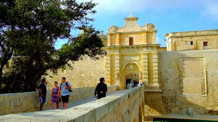 hanedan arması : MDINA, MALTA - JUNE 14, 2018: The arched bridge, in front of the medieval stone Main (Vilhena) Gate, leads to the fortified city, on June 14 in Mdina. Stok Video