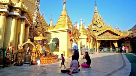 sztúpa : YANGON, MYANMAR - FEBRUARY 17, 2018: The worshipers pray at the Buddha images of Sule Pagoda, little boy with father performs the Buddhist ritual of ringing the bell, on February 17 in Yangon.
