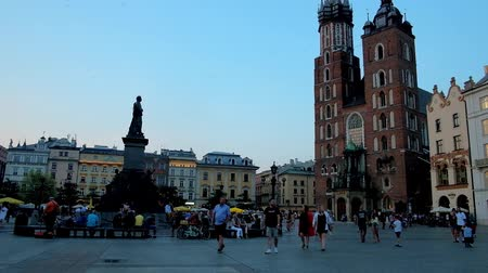 sukiennice : KRAKOW, POLAND - JUNE 11, 2018: The twilight sky over the Main Market Square and its main landmarks - St Marys Basilica and Adam Mickiewicz monument, on June 11 in Krakow. Stock Footage