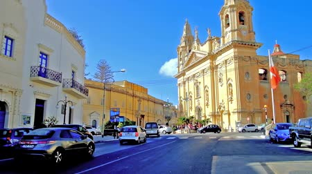 мальтийский : NAXXAR, MALTA - JUNE 14, 2018: The busy Victory Square with its main object - the Parish Church of Our Lady of Victories - the notable landmark of the village, on June 14 in Naxxar. Стоковые видеозаписи
