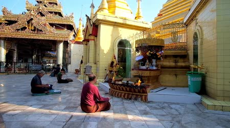 paya : YANGON, MYANMAR - FEBRUARY 17, 2018: The worshipers pray in Sule Pagoda, sitting on the floor in front of Lord Buddha image, on February 17 in Yangon.