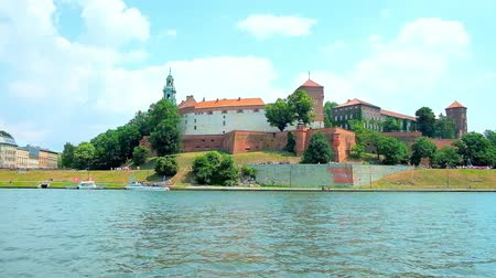 wawel : Enjoy the picnic on the bank of Vistula river, opening the view on medieval Wawel Castle with preserved ramparts, high towers and lush green garden around it, Krakow, Poland. Stock Footage