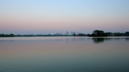 externalisation : The calm surface of Inya lake reflects the clear sunset sky, silhouette of dark trees and high-rises on the distance, Yangon, Myanmar.