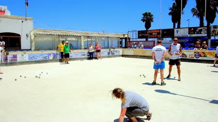 мальтийский : BUGIBBA, MALTA - JUNE 14, 2018: The bocci game (bowlsboules) is popular sport activity in Maltese resorts, locals and tourists enjoy it in small sand field, on June 14 in Bugibba. Стоковые видеозаписи