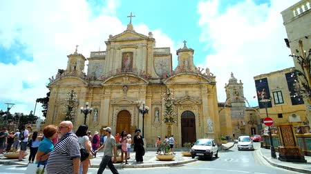 мальтийский : RABAT, MALTA - JUNE 16, 2018: The crowded San Pawl Square with historic Collegiate church of St Paul, that is the notable city landmark and object of tourist interest, on June 16 in Rabat. Стоковые видеозаписи
