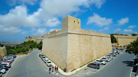 takımadalar : MDINA, MALTA - JUNE 14, 2018: The medieval St Peters bastion of Mdina fortress with modern car parking in moat, on June 14 in Mdina. Stok Video
