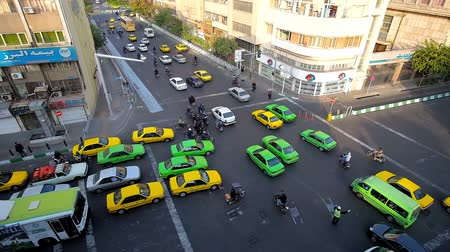 persie : TEHRAN, IRAN - OCTOBER 25, 2017:  Busy traffic on the intersection of Amir Kabir and Pamenar streets, yellow and green taxies and public buses drive in different directions, on October 25 in Tehran Dostupné videozáznamy