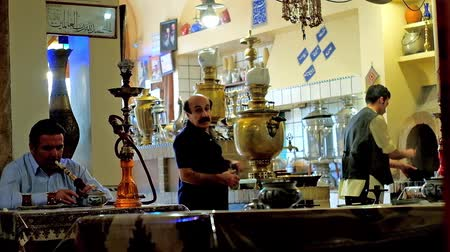 sousedství : TEHRAN, IRAN - OCTOBER 25, 2017: Hall of traditional Azari Chaykhaneh (teahouse) with local man, smoking shisha and a view on samovars with tea pots on the background, on October 25 in Tehran. Dostupné videozáznamy