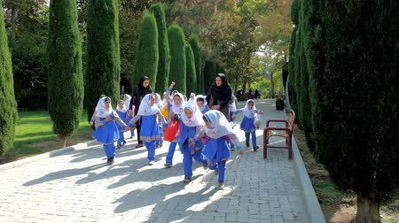 silk road : TEHRAN, IRAN - OCTOBER 25, 2017: The group of little Iranian schoolgirls, dressed in uniforms and hijabs, runs and plays during excursion to Laleh Park, on October 25 in Tehran.
