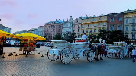 kamienice : KRAKOW, POLAND - JUNE 11, 2018: The old-fashioned horse-drawn carriages in Plac Mariacki (Main or Market Square) are perfect choice to take romantic evening journey in Old Town, on June 11 in Krakow.