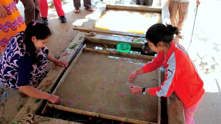 dut : PINDAYA, MYANMAR - FEBRUARY 19, 2018: The Shan Paper production in progress - young artisans create the pattern of flower petals and leaves on surface of raw paper dough, on February 19 in Pindaya.