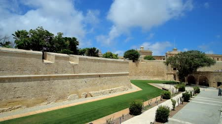 canto : Walk along the huge city walls of old Mdina, surrounded by scenic park, with a view on historic De Redin Bastion, Malta.