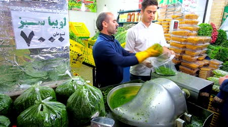 persie : TEHRAN, IRAN - OCTOBER 25, 2017: The vendors of herbs stall in Tajrish Bazaar chop the sabzi leaves in cutting machine, pack it and put on the showcase, on October 25 in Tehran Dostupné videozáznamy