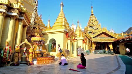 paya : YANGON, MYANMAR - FEBRUARY 17, 2018: The Buddhist devotees pray at the shrines of Sule Pagoda, decorated with carved golden decors, traditional patterns and pyatthat roofs, on February 17 in Yangon. Stock Footage