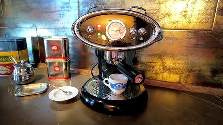ristretto : NAPLES, ITALY - SEPTEMBER 19, 2018: Preparing of waking cup of morning espresso in luxury vintage styled FrancisFrancis home coffee machine with Illy ESE coffee pod, on September 19 in Naples.