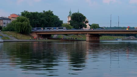 епископ : The view on Grunwald Bridge across Vistula river with fast riding trams and the bell towers of St Michael the Archangel Church on Skalka, seen on the background, Krakow, Poland.