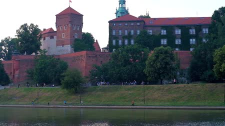 fortresses : The green Wawel Hill with rampart and buildings of the castle and the statue of Dragon (Smok Wawelski) on the bank of Vistula river, Krakow, Poland.