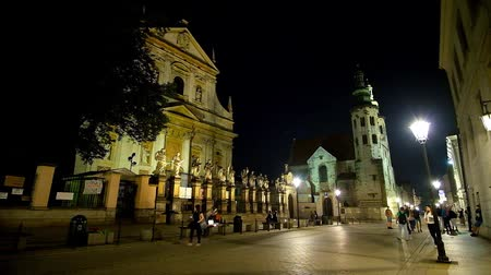 romanesk : KRAKOW, POLAND - JUNE 12, 2018: The evening illumination of Grodzka street with a view on facade of St Peter and Paul church and the bell towers of St Andrew Church, on June 12 in Krakow. Stok Video