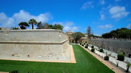 canto : The huge St Peters Bastion of Mdina fortress, surrounded by green lawn and trimmed bushes of local park, stretching along historic moat, Malta.