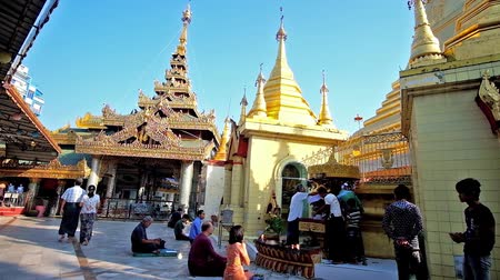 paya : YANGON, MYANMAR - FEBRUARY 17, 2018: The numerous worshipers on the morning pray in Sule Pagoda with numerous golden shrines and image houses, on February 17 in Yangon. Stock Footage