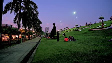 mianmar : YANGON, MYANMAR - MARCH 2, 2018: Inya lake park is best place to relax on the lawn, watch the passers by and riding cars, enjoy picnic with friends and family and meet the sunset, on March 2 in Yangon
