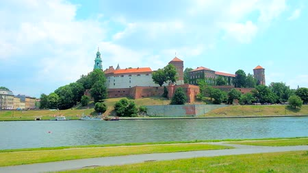 bank tower : The scenic riverside park with a view on medieval Wawel Castle across the Vistula river, Krakow, Poland. Stock Footage