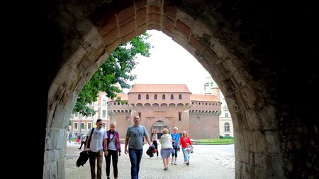 fortress : KRAKOW, POLAND - JUNE 12, 2018: Pedestrians walk through the arch of St Florian Gate (Brama Florianska) with a view on Barbikan fortified outpost, located in Planty park, on June 12 in Krakow.