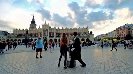 sukiennice : KRAKOW, POLAND - JUNE 12, 2018: The mime artist in black vintage coat and cylinder hat entertains the passers by and poses for photos with tourists in Main Market Square, on June 12 in Krakow.