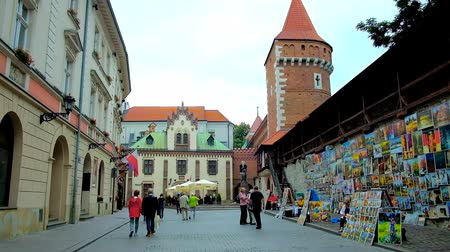 kamienice : KRAKOW, POLAND - JUNE 12, 2018: Architectural ensemble of Pijarska street with tower of St Florian Gate, Czartoryski Palace, old mansions and art fair along the city wall, on June 12 in Krakow.