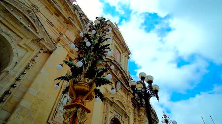 мальтийский : Fast moving clouds over the St Pauls Parish Church of Rabat, decorated with scenic garlands and lamps to the city feast, Malta.