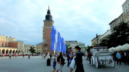 kamienice : KRAKOW, POLAND - JUNE 12, 2018: The  Market Square is the center of Old Town (Stare Miasto) with many pedestrians, tourist cafes, historic  landmarks and riding carriages, on June 12 in Krakow. Stock Footage