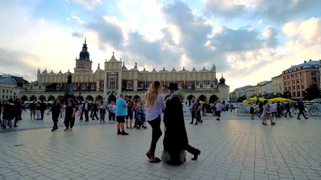 manor : KRAKOW, POLAND - JUNE 12, 2018: The mime artist makes performance in Main Market Square with a view on Cloth Hall (Sukiennice) handicraft market behind him, on June 12 in Krakow.