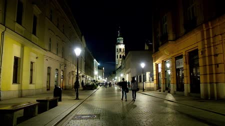 kamienice : KRAKOW, POLAND - JUNE 12, 2018: Evening walk along the Grodzka street with soft illumination and tall bell tower of St Andrew Church on background, on June 12 in Krakow.