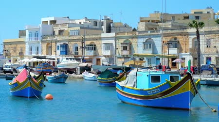 мальтийский : MARSAXLOKK, MALTA - JUNE 18, 2018: The line of old edifices along the Xatt Is-Sajjieda seaside promenade and the old wooden luzzu boats in marina of the village, on June 18 in Marsaxlokk.