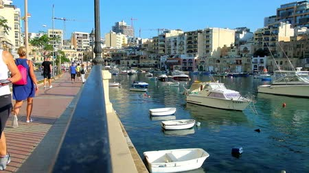 tersane : ST JULIANS, MALTA - JUNE 20, 2018: The busy street of George Borg Olivier stretches along the Spinola Bay harbor with old fishing boats and smal dinghies, on June 20 in St Julians.