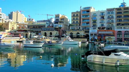 takımadalar : ST JULIANS, MALTA - JUNE 20, 2018: The fishing boats in Spinola Bay harbor with modern residential buildings and coastal cafes on the background, on June 20 in St Julians.