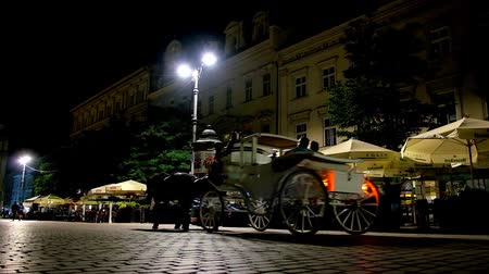 kamienice : KRAKOW, POLAND - JUNE 12, 2018: The silhouette of horse-drawn carriage slowly rides along the dark poor lighted Main Market Square, on June 12 in Krakow