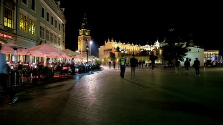 kamienice : KRAKOW, POLAND - JUNE 12, 2018: The dark evening in Main Market Square with a view on illuminated Town Hall Tower, Cloth Hall, outdoor restaurants and walking tourists, on June 12 in Krakow.