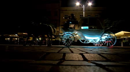 kamienice : KRAKOW, POLAND - JUNE 12, 2018: The  horse-drawn carriage slowly rides along the outdoor restaurants at late evening in dark Main Market Square, on June 12 in Krakow. Stock Footage