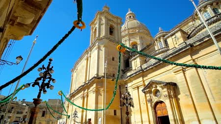 manor : The festival garlands and lanterns decorate San Nikola street  at the St Nicholas Parish Church with tall stone walls, huge bell tower and dome, Siggiewi, Malta Stock Footage