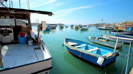 tersane : MARSAXLOKK, MALTA - JUNE 18, 2018: The fishing fleat of the village consists of old boats and colorful Maltese luzzu vessels, especially popular among the tourists, on June 18 in Marsaxlokk.