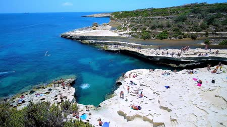 солнечные ванны : MARSAXLOKK, MALTA - JUNE 18, 2018:  Delimara coast boasts one of most stunning beaches in country - the natural limestone St Peters Pool, popular among locals and tourists, on June 18 in Marsaxlokk.
