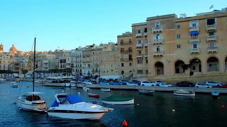 lápide : SENGLEA, MALTA - JUNE 18, 2018: The yachts luzzu and dghajsa boats at the shore of the fortified L-Isla (Senglea), one of the stunning medieval cities of Valletta Grand Harbour, on June 18 in Senglea. Stock Footage