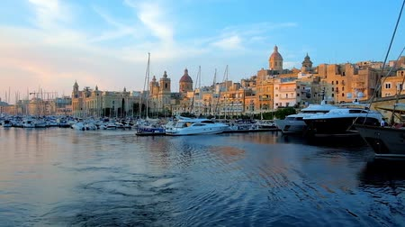 tersane : BIRGU, MALTA - JUNE 18, 2018: The sunset rays illuminate the medieval edifices and churches along Vittoriosa Marina with moored yachts and boats, rocking on the gentle waves, on June 18 in Birgu.
